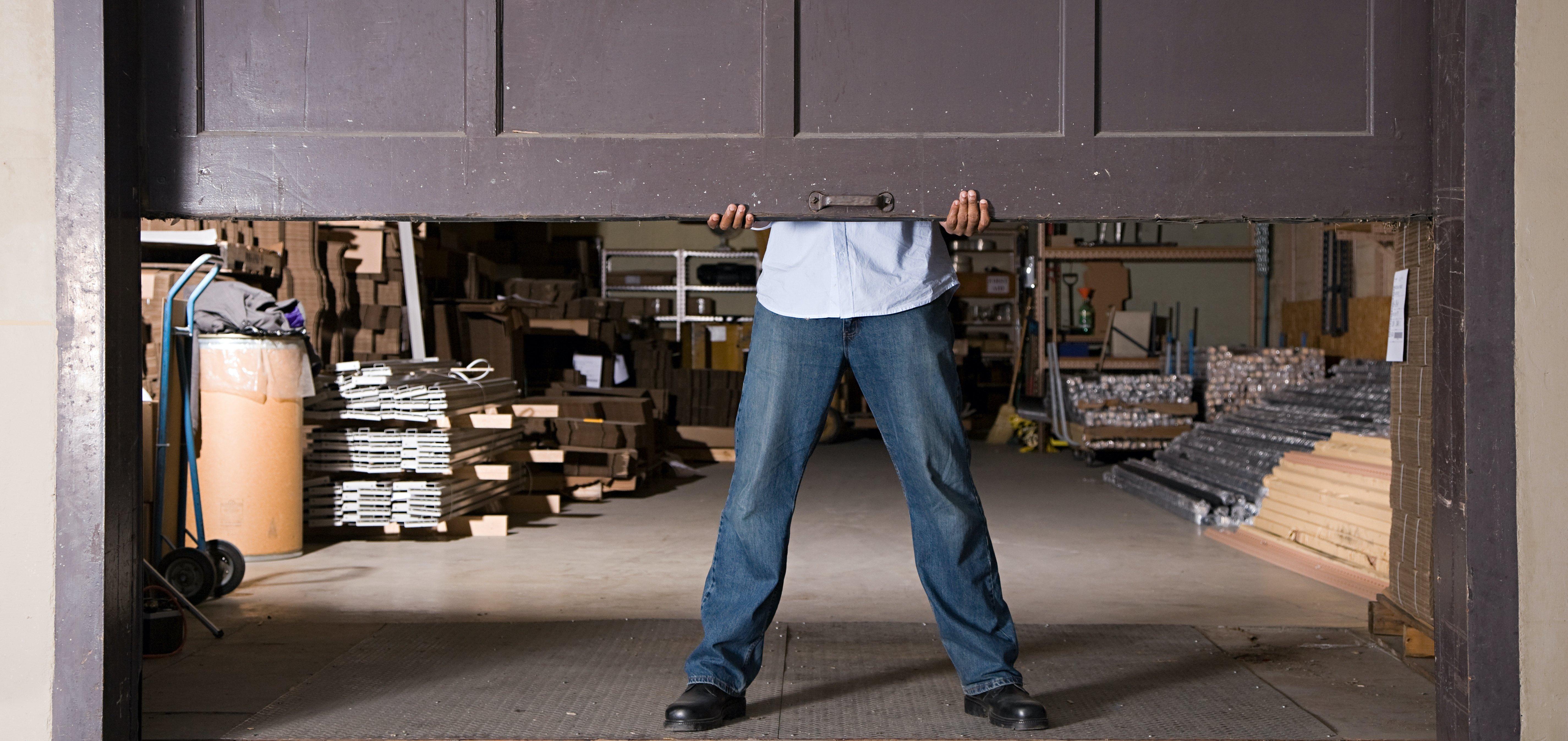 Man holding up garage door