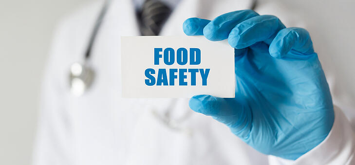 Inspector holding a food safety card