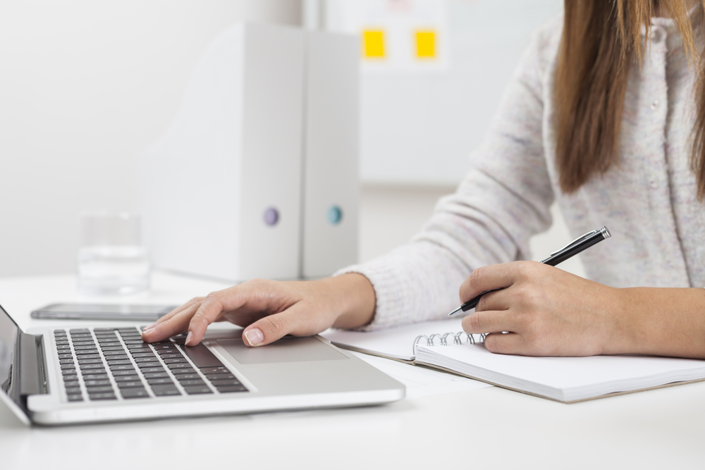 woman taking notes on computer and notebook